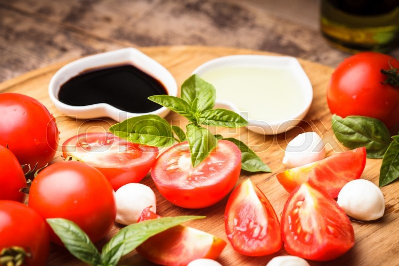 Stock image of 'Ingredients for caprese salad on the wooden board. Tomatoes, basil and baby mozzarella, italian food'