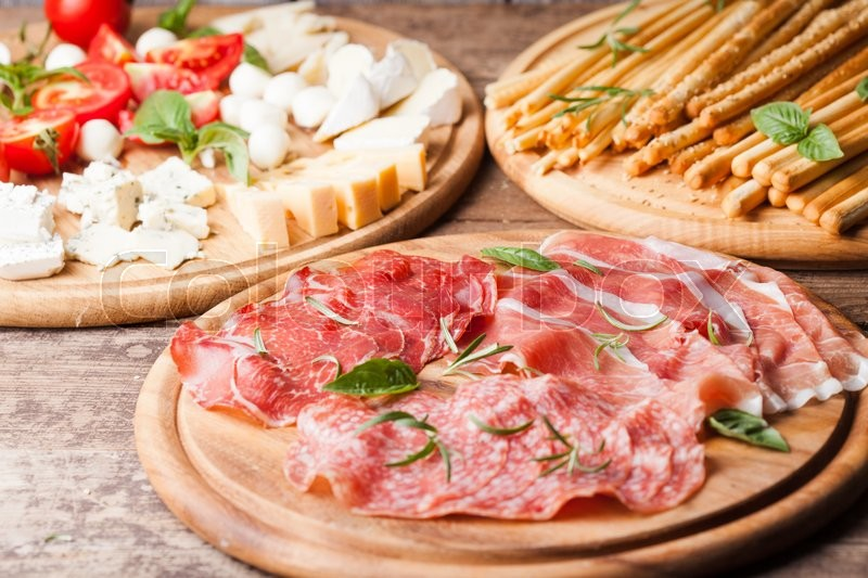 Stock image of 'Italian appetizer - various types of ham, cheese and grissini'