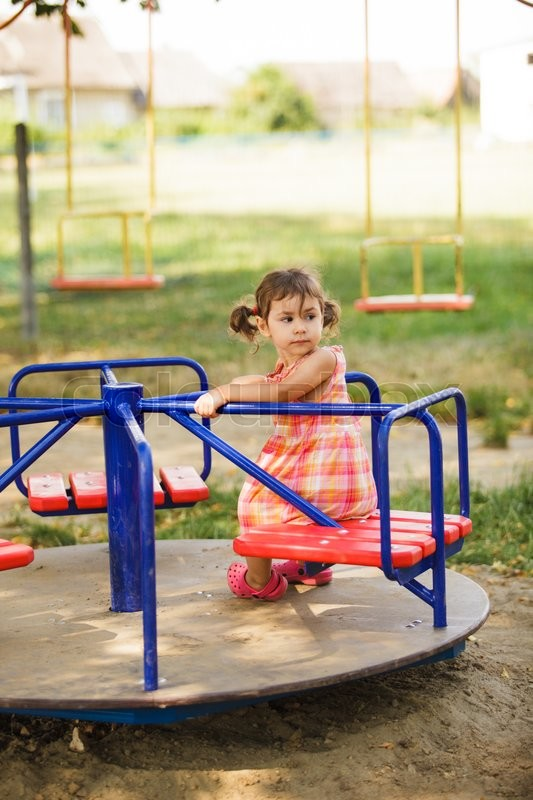 Stock image of 'Little girl on the carousel at the playground'
