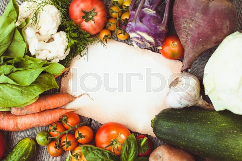 Stock image of 'Old recipe on the table with vegetables with copy space'