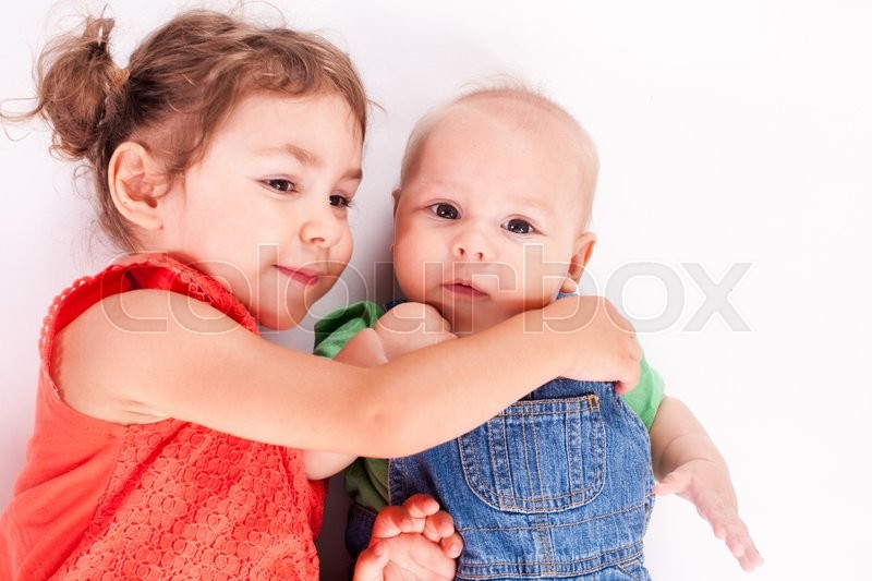 Stock image of 'Adorable family. Sister and brother isolated on white'