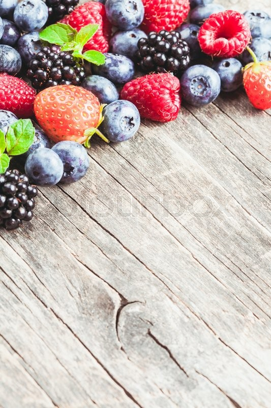 Stock image of 'Summer wild berries over shabby wooden  background. Raspberry, strawberry, blackberry and blueberry on the table'