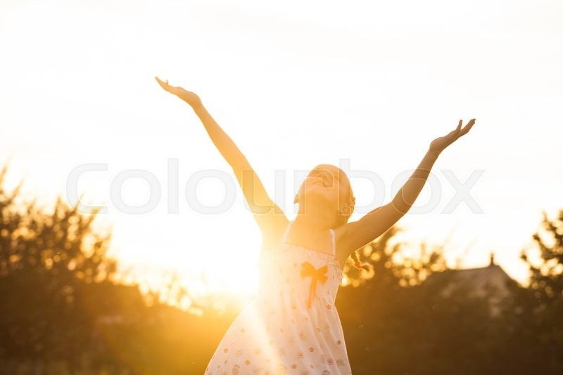Stock image of 'The little girl enjoys the sunset, she looks up and spreads his hands with pleasure'