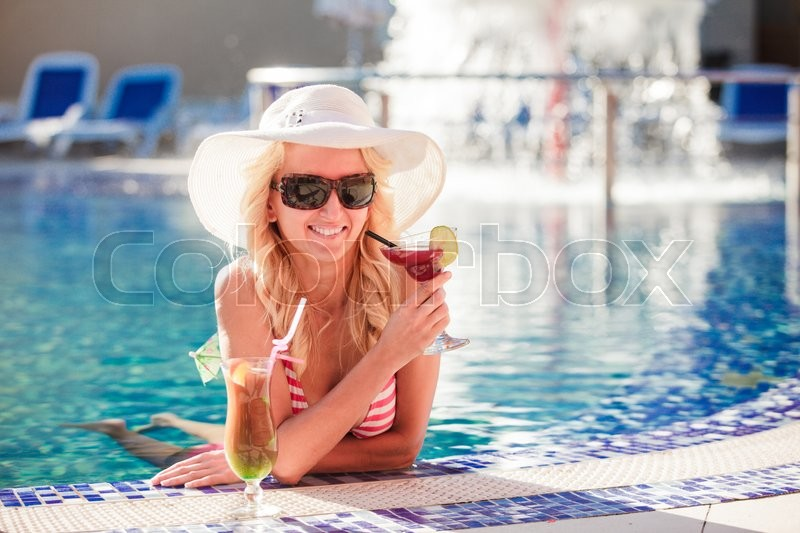 Stock image of 'Blonde woman in hat at the swimming pool'
