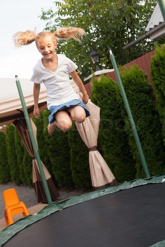 Stock image of 'Girl enthusiastically jumping on the trampoline. Moment flight'