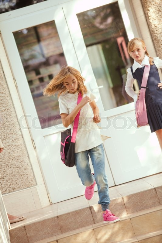 Stock image of 'Two schoolgirls outdoors near the door of school building'