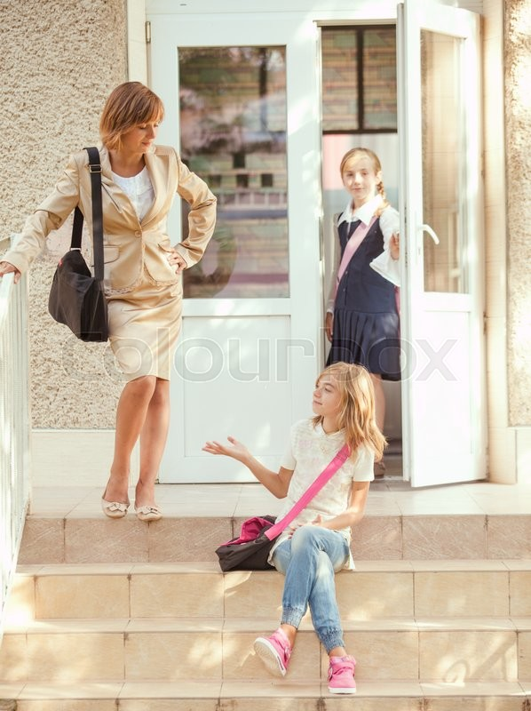Stock image of 'Three schoolgirls outdoors near the door of school building'