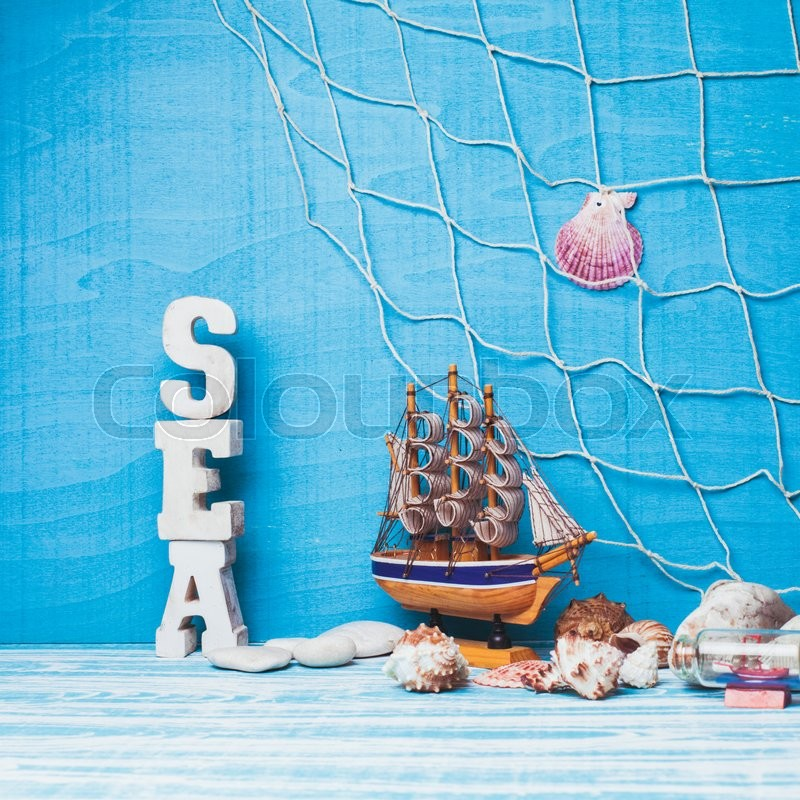 Stock image of 'Beautiful sea composition with toy sailboat, seashell, glass bottle and fishing net on blue background'