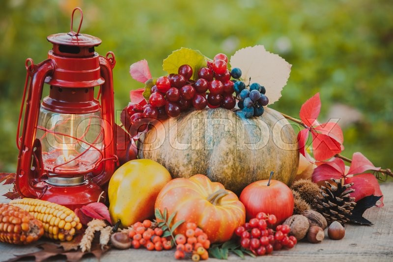 Stock image of 'Fruits and nuts, pumpkins on the table outdoor and kerosene lamp - cozy autumn'