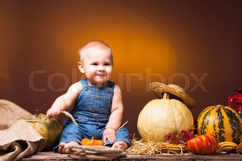 Stock image of 'Cute baby with ears of wheat in the hands posing on the background of pumpkins.'
