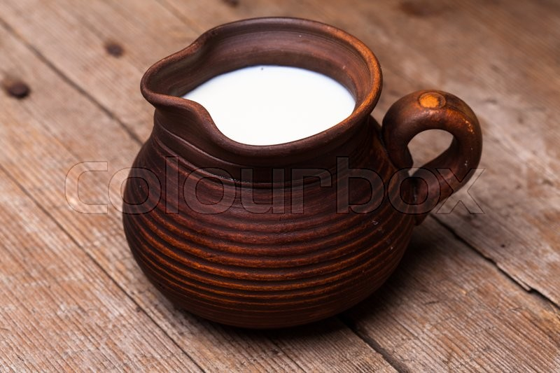 Stock image of 'Milk in earthen jug on rustic woodtn table'