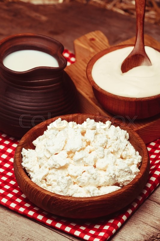 Stock image of 'Milk, sour cream and curd on a wooden rustic board'