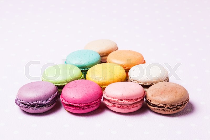 Stock image of 'Colorful macaroons - french dessert over pink polka dot napkin'