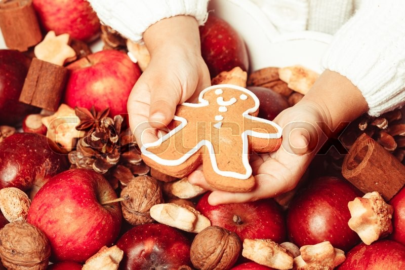 Stock image of 'Child's hands hold a red apple and gingerman cookie'