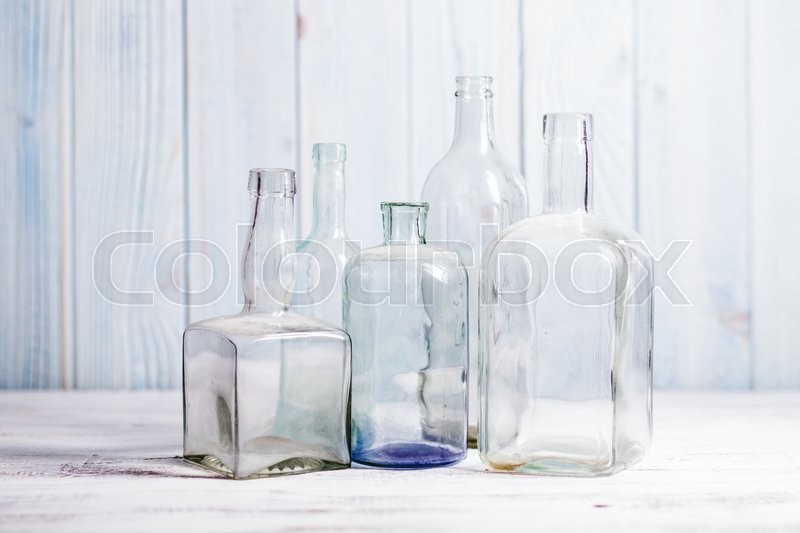 Stock image of 'Collection of empty vintage glass bottle on a wooden background.'
