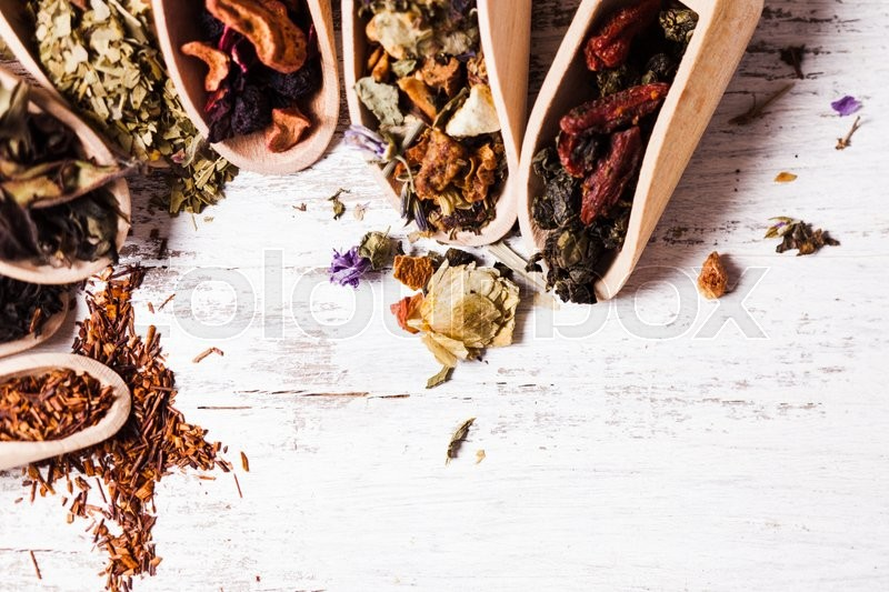 Stock image of 'Various of dried tea in wooden scoops on white shabby table'
