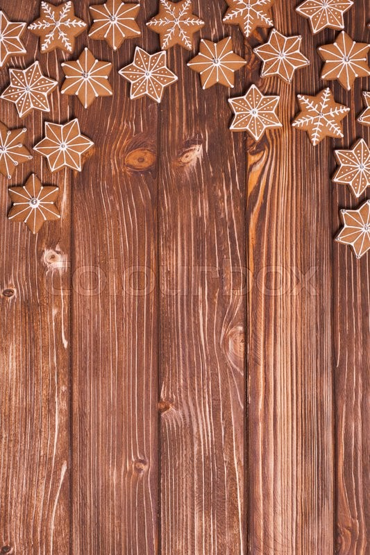 Stock image of 'Frame of gingerbreads on a wooden background.'
