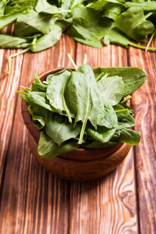 Stock image of 'Fresh green whole sorrel leaves in a wooden bowl'