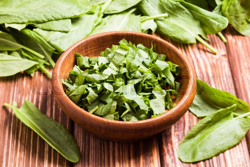 Stock image of 'Fresh green sorrel in a wooden bowl'