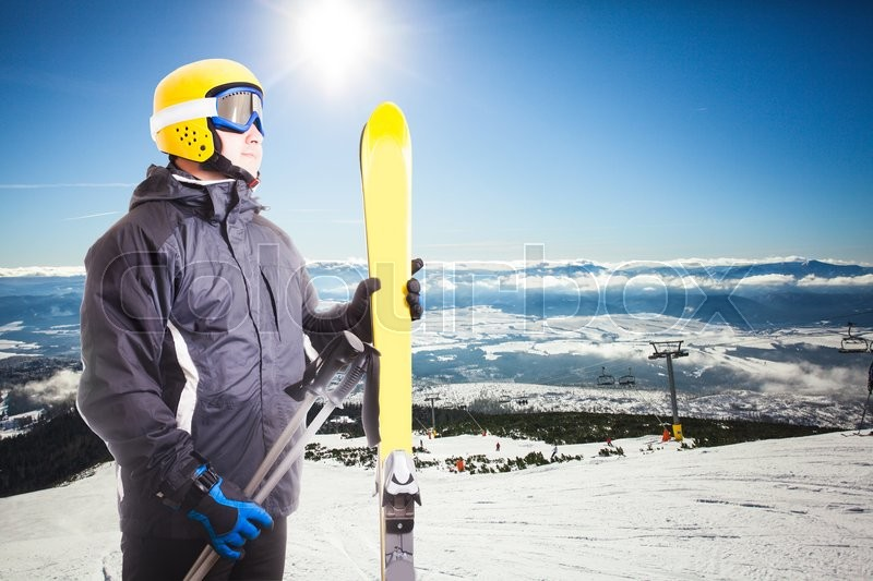 Stock image of 'Ski slope in High Tatras mountains on the background and skier portait with equipment'