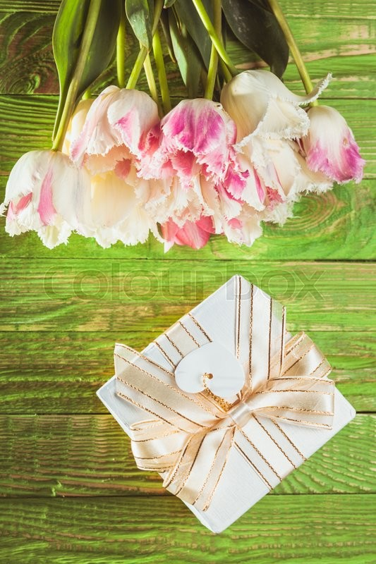 Stock image of 'Pink tulips and gift box on a green wooden table'