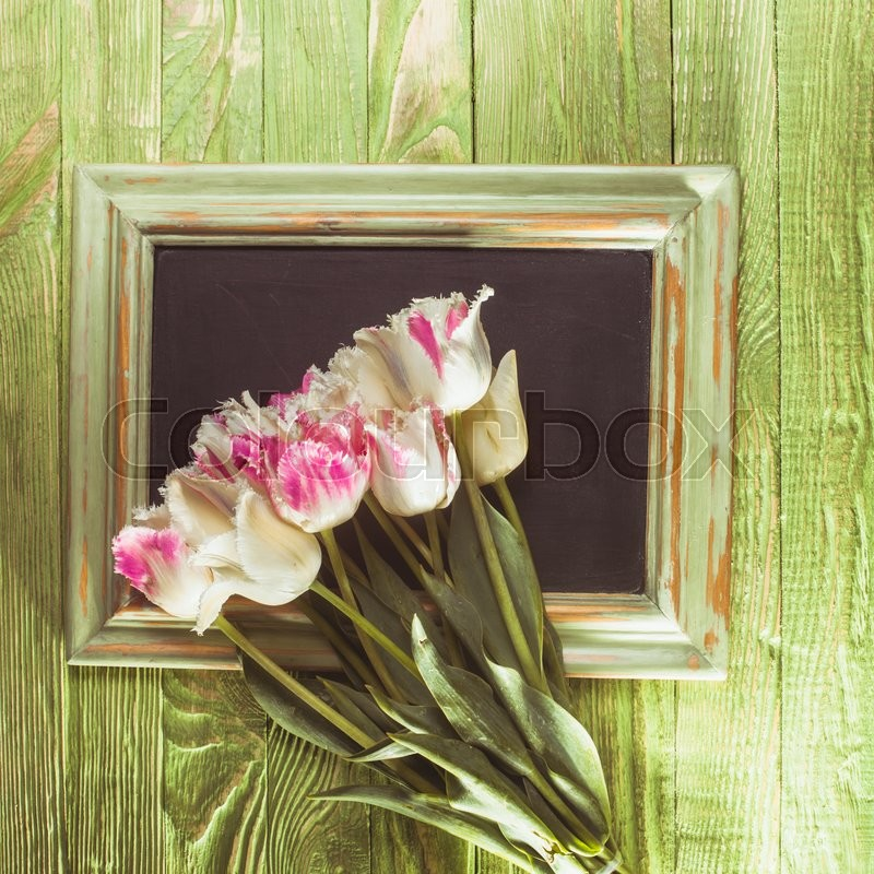 Stock image of 'Pink tulips on a green wooden chalkboard with copy space. Teacher's day concept'