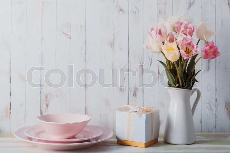 Stock image of 'White vase with delicate shades armful of tulips on a wooden background'