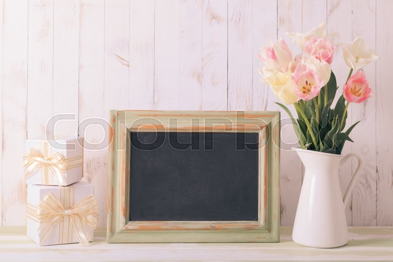 Stock image of 'Pink tulips in jug and green wooden chalkboard. Teacher's day concept'