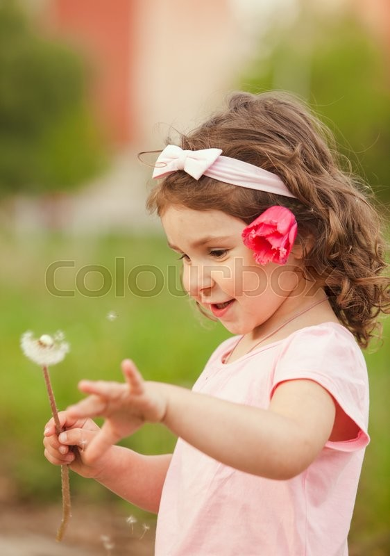Stock image of 'The little girl with a red flower in her hair played with dandelion'