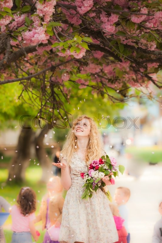 Stock image of 'Girl under the sakura tree with flowers in hands enjoys the blossom'