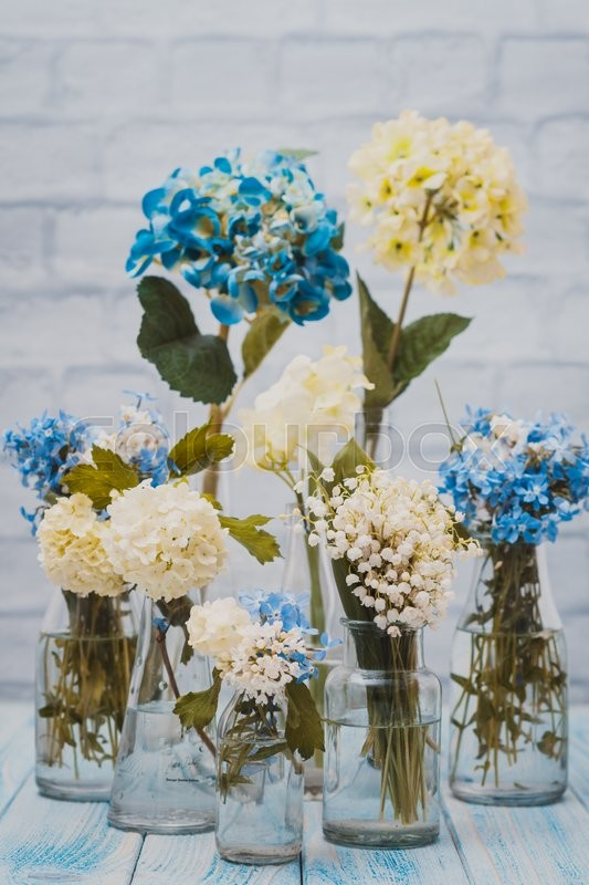 Stock image of 'Flowers in bottles over white wall, vintage styled'