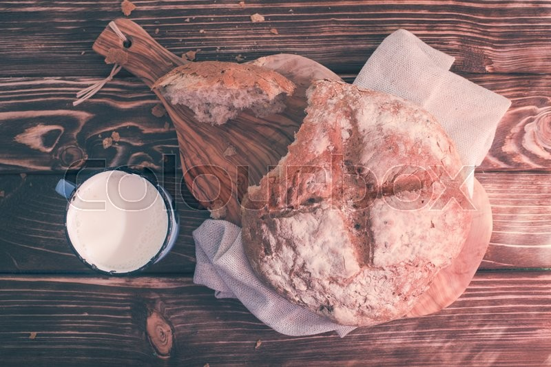 Stock image of 'Piece of bread and cup of milk. Morning rustic still life'