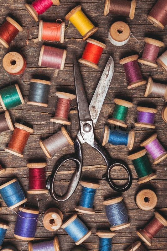 Stock image of 'Retro wooden sewing spools with colourful threads and vintage scissors'