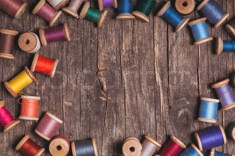 Stock image of 'Retro wooden sewing spools with colourful threads over vintage wooden background'