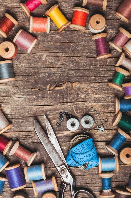 Stock image of 'Retro scissors, textile and sewing threads on the wooden table'