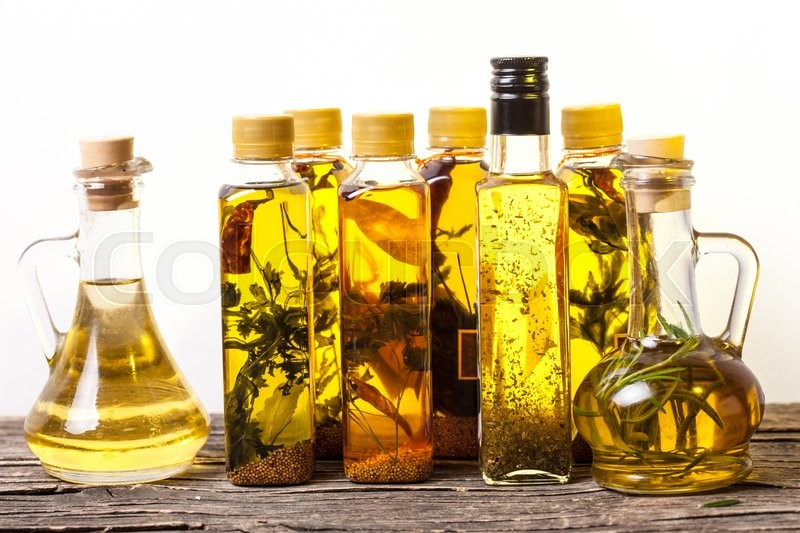 Stock image of 'Assortment of spicy oils with herbs and spices in different bottles over white background'