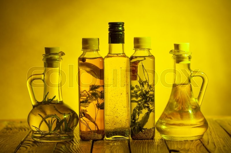 Stock image of 'Assortment of spicy oils with herbs and spices in different bottles'