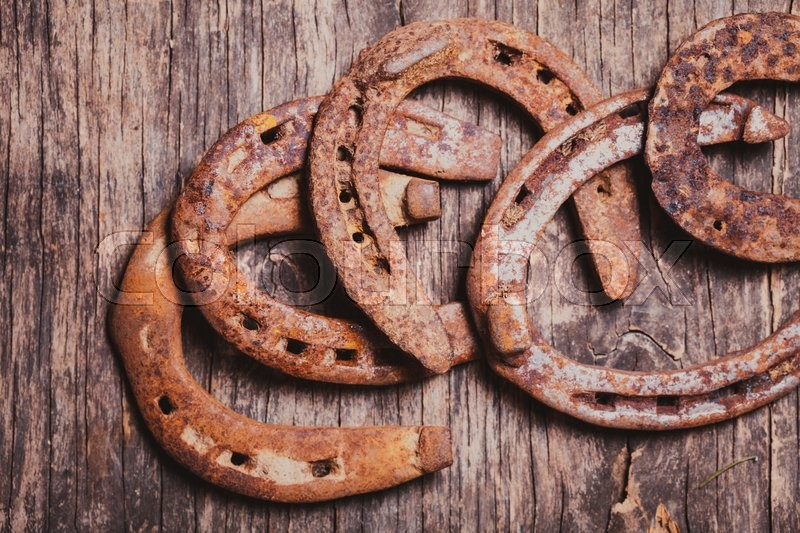 Stock image of 'Close-up old rusty horseshoe on wooden background'