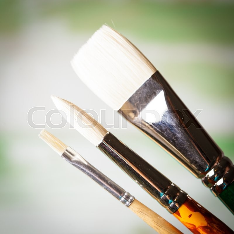 Stock image of 'Various types of paint brushes over the defocused painting'