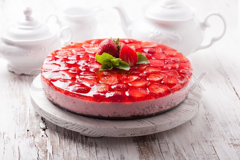 Stock image of 'Strawberry cake on white wooden plate with mint leaf'