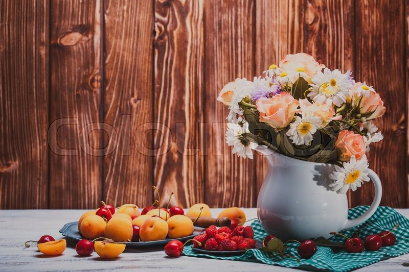 Stock image of 'Summer still life with peaches, raspberries, cherries and flowers on a wooden table'