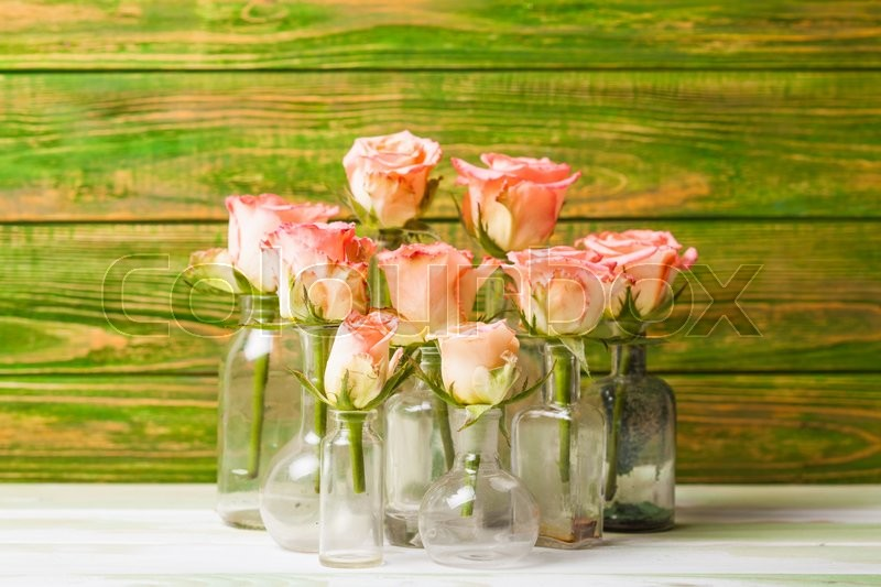 Stock image of 'Pink roses in vintage bottles, home decor'