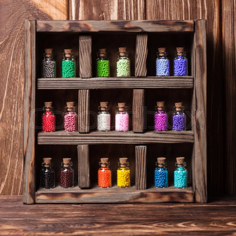 Stock image of 'Beads in mini retro glass bottles, vintage box'