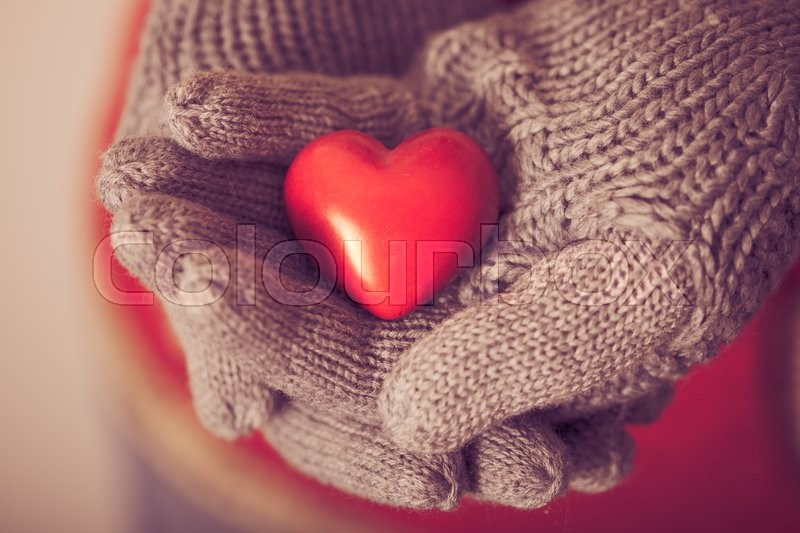 Stock image of 'Close-up of hands in grey knitted mittens holding red heart'