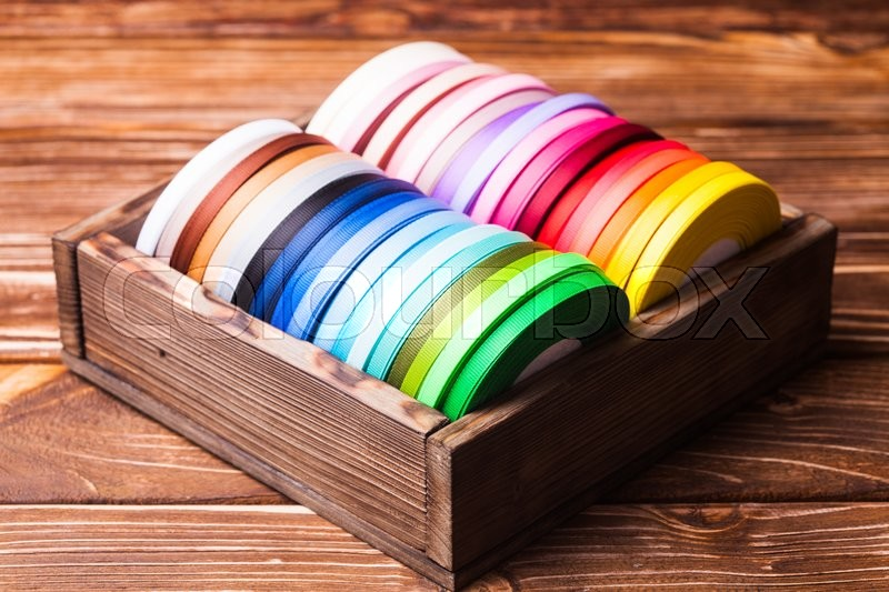 Stock image of 'Various colors ribbon bobbins in vintage wooden box'