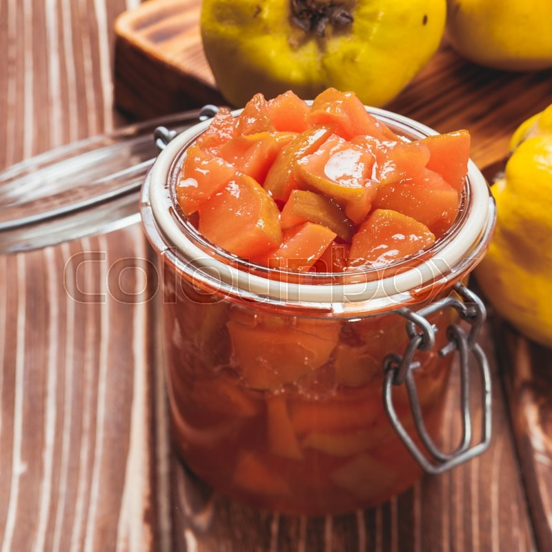 Stock image of 'Quince jam in the glass jar and fruits on the background'