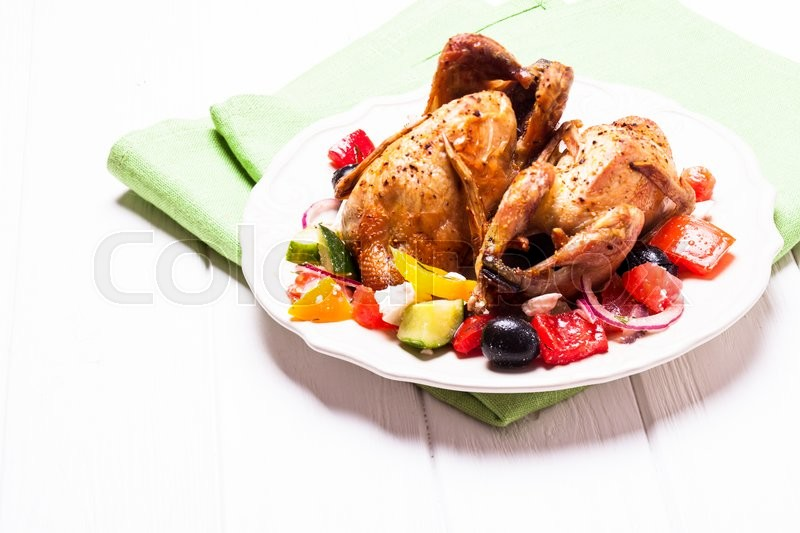 Stock image of 'Baked whole quail and fresh vegetable salad in white plate on table with green napkin'