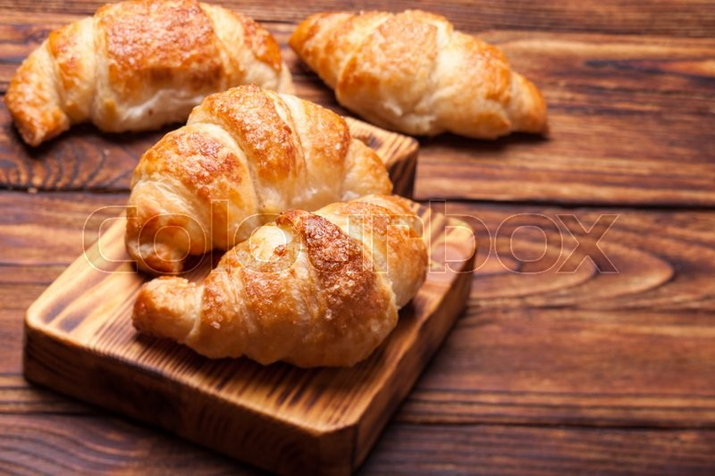 Stock image of 'Two  delicious croissants on a wooden cutting board'