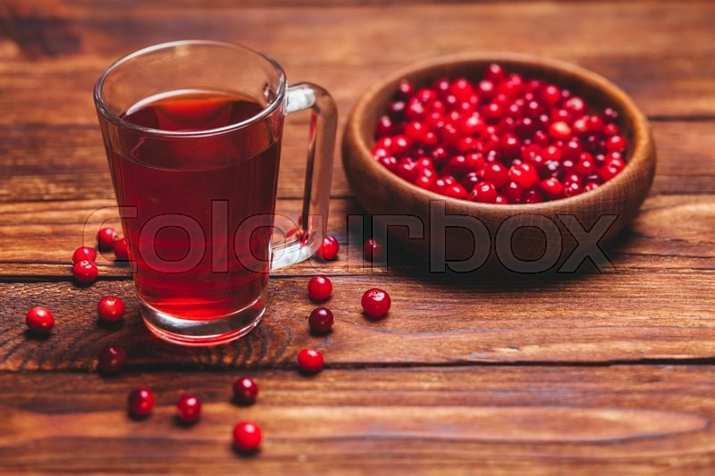 Stock image of 'Cranberry tea in a glass cup on a wooden table'