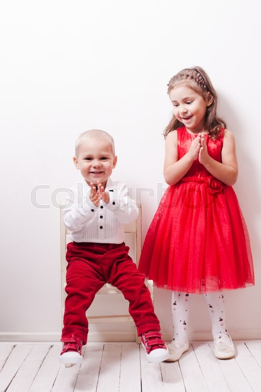 Stock image of 'Little boy in red pants and a girl in a red dress posing for photos in harmony'